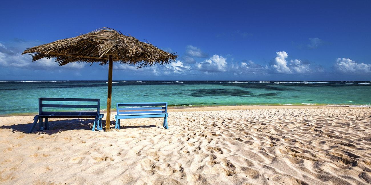 Vita sandstränder med parkbänkar och regnskydd