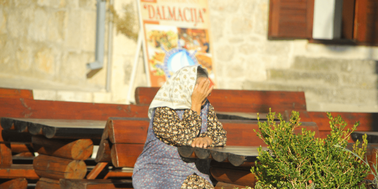 En äldre kvinna med sjal sitter på en uteservering