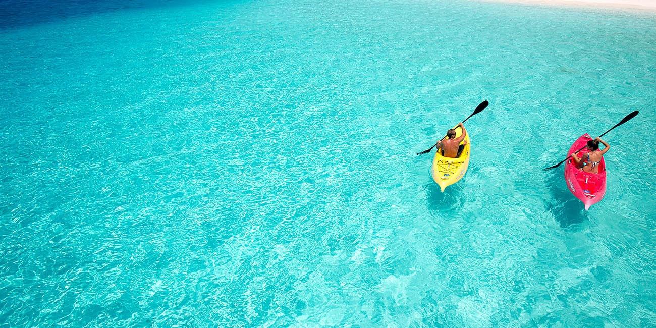 Hyr båt och paddla över turkost genomskinligt vatten