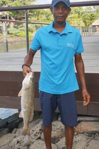 Han visar stolt upp fisken som ska ätas