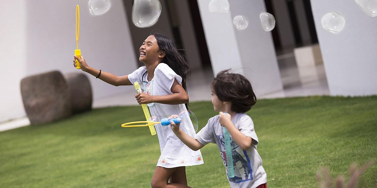 Lyckliga barn som leker hos med såpbubblor