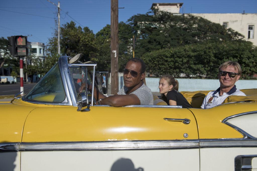 Troligtvis far och dotter i en gul veteranbil