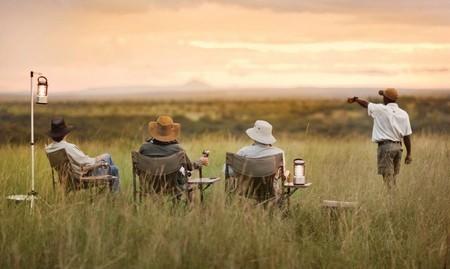 Män på safari blickar över Serengeti